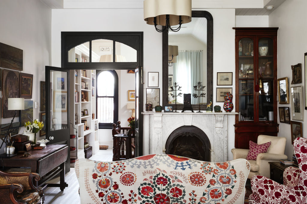The fabulous Prahran East home of Tigger Hall, interior designer, organiser of Como by Design, and founder of Nine Muses Textiles. The living room. Sofa covered in Suzani purchased in Istanbul. Chair covered in Penny Morrison Arabella Red. Dulux Natural White is used on the walls. Styling: Annie Portelli.