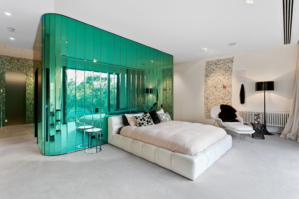 One of the bedrooms has a tinted mirror feature wall, which behind lies a walk in wardrobe.