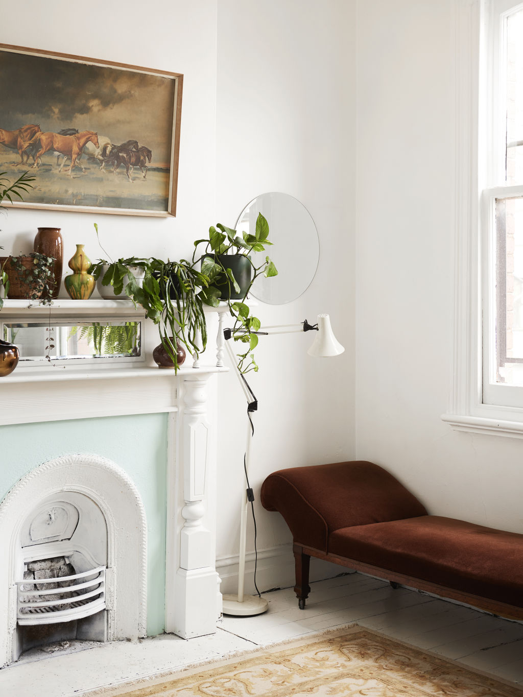 The light in the house streams into the second floor. It's the only fully white room in the house, so in true Jenna style, she had to paint the fireplace just to 'add a little something-something'. Daybed, lamp and painting are secondhand. Styling: Annie Portelli.