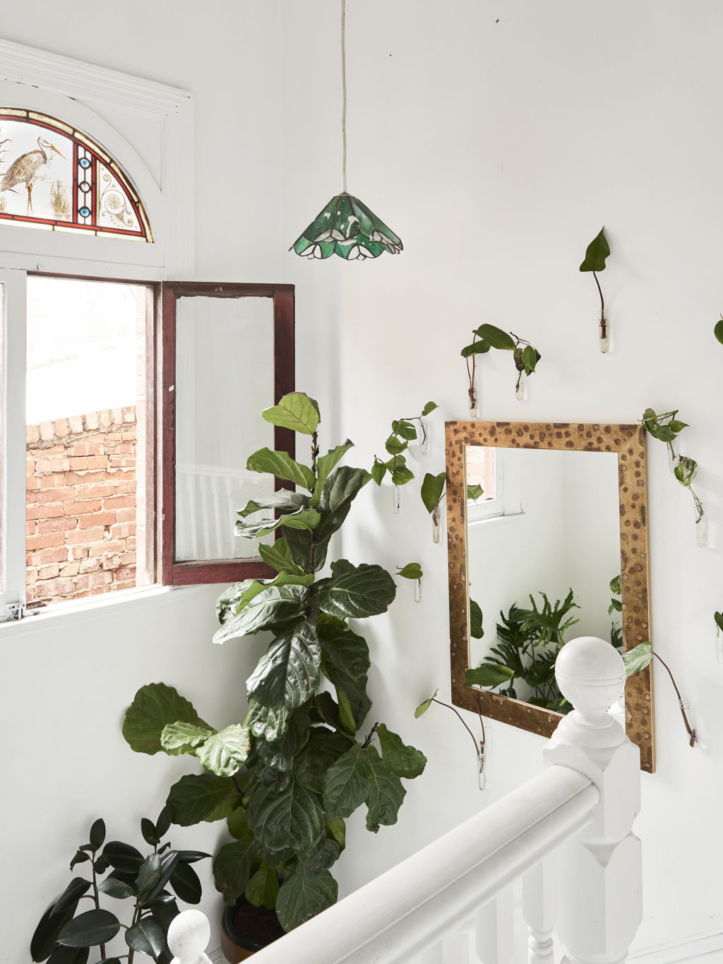 The stairway, where Jenna drinks her morning coffee, is 'a light-filled dream', she says. It showcases the little quirky design additions to the home, including the stained glass window and glass lighting fixtures. Styling: Annie Portelli.