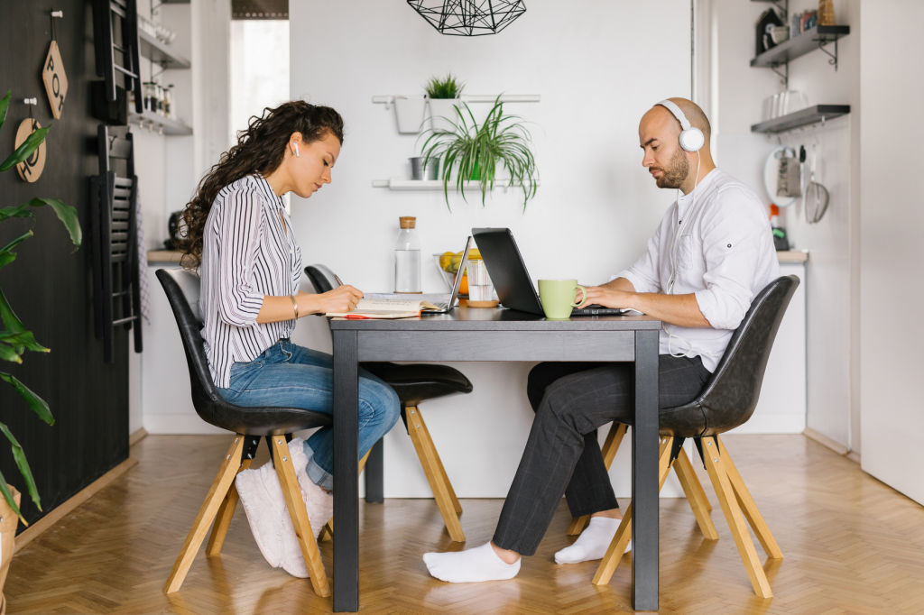 Young married couple working from home, they are sitting in their dining room.