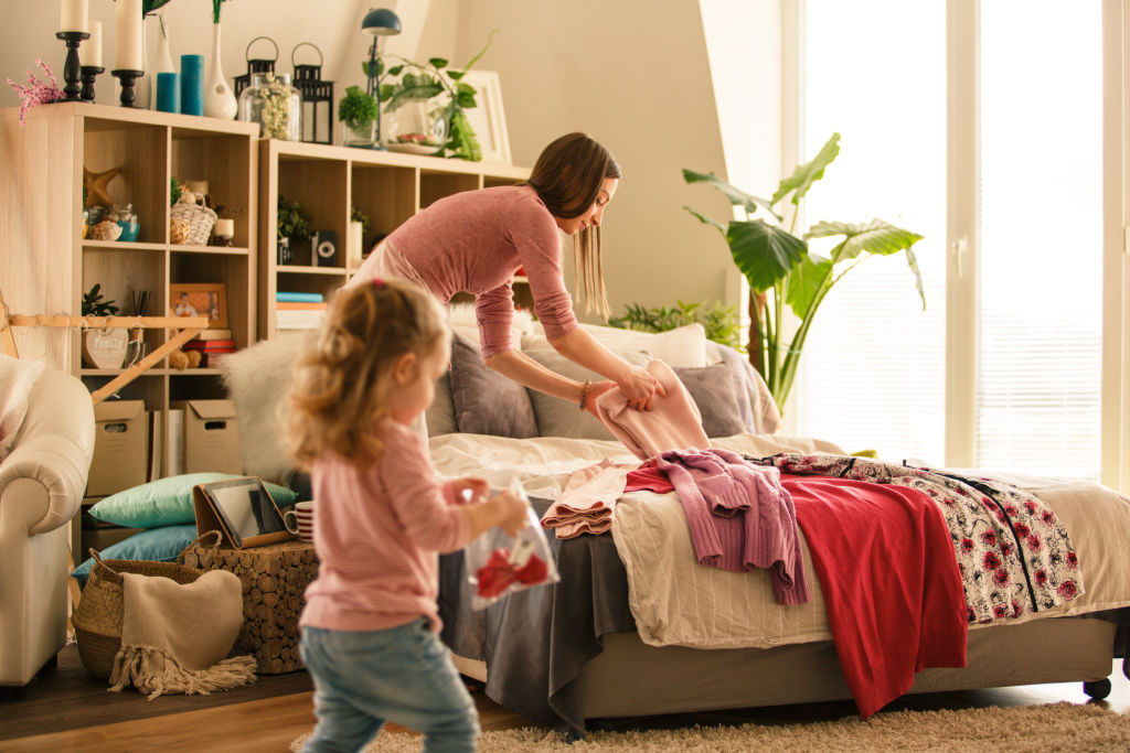 Mother and her little baby girl folding clothes in their bedroom. They are preparing for packing for vacation.