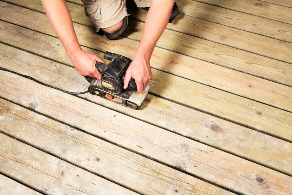 A belt sander makes it easier to prepare worn decking boards for refinishing.