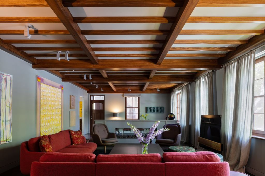 The main living room is a grid of beefy timbers, period appropriate and supporting the new second-level structure above.