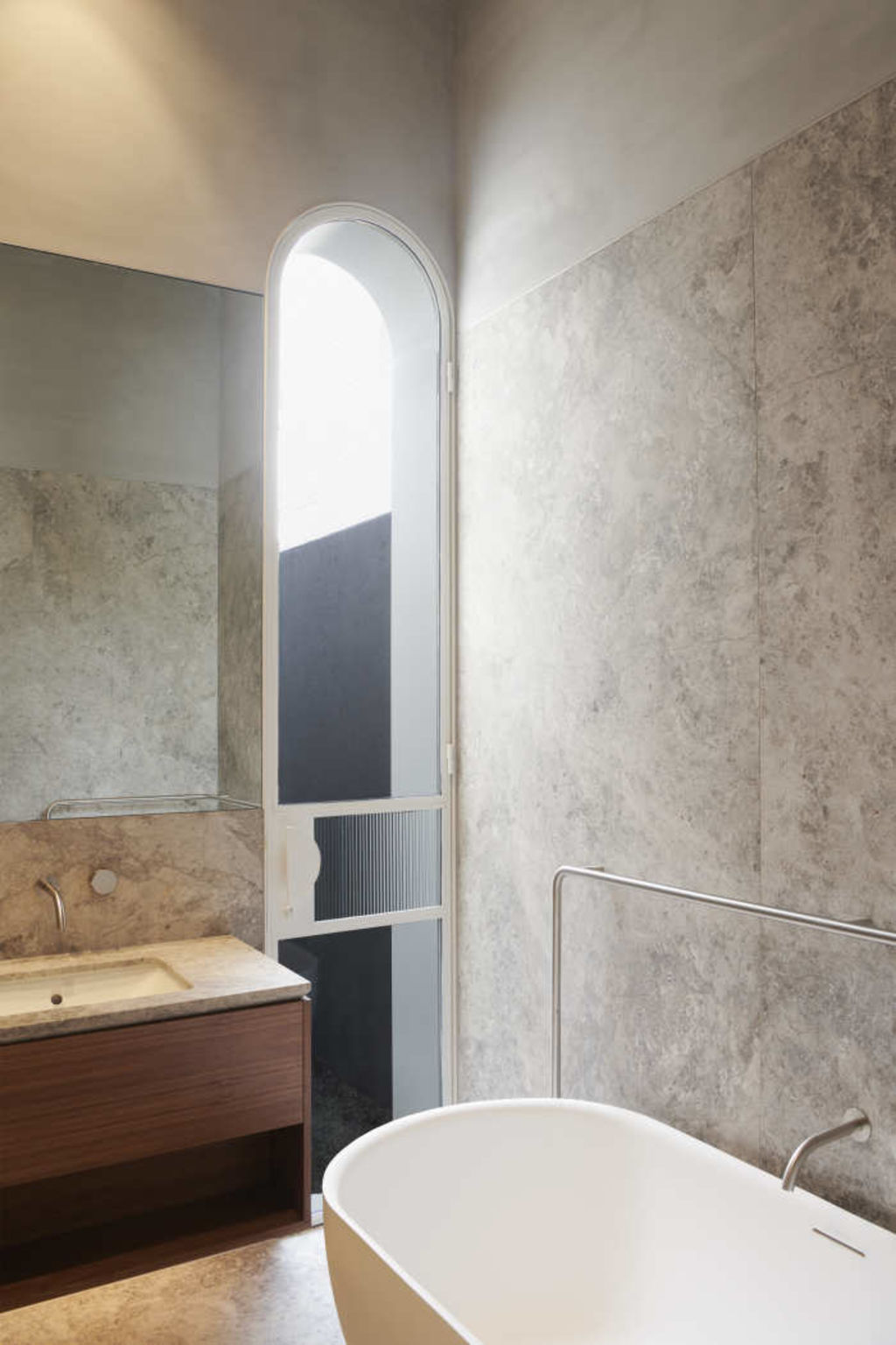 Curves echoing curves in the limestone-clad bathroom. For Toorak architecture story.
