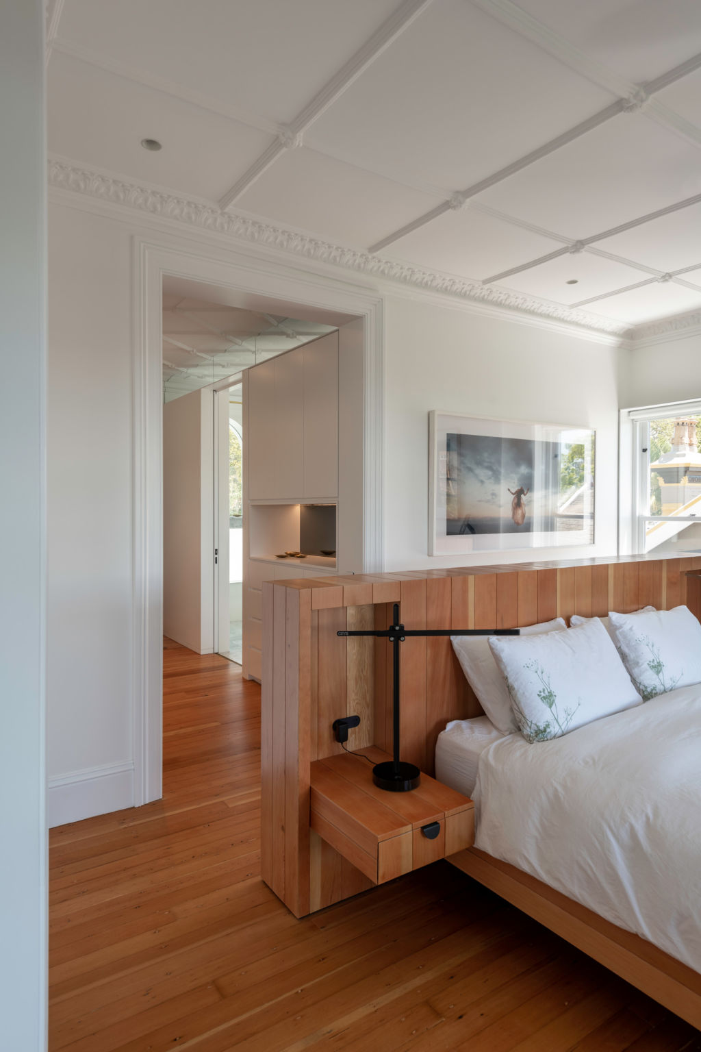 Behind the custom-made bedhead and between the wall and ceiling, a clerestory preserves the plasterwork. Kirribilli cool.