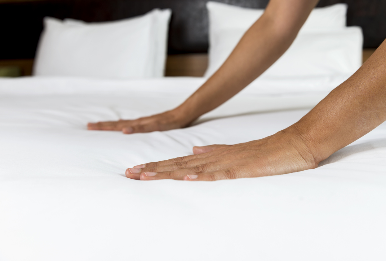 Woman making bed.