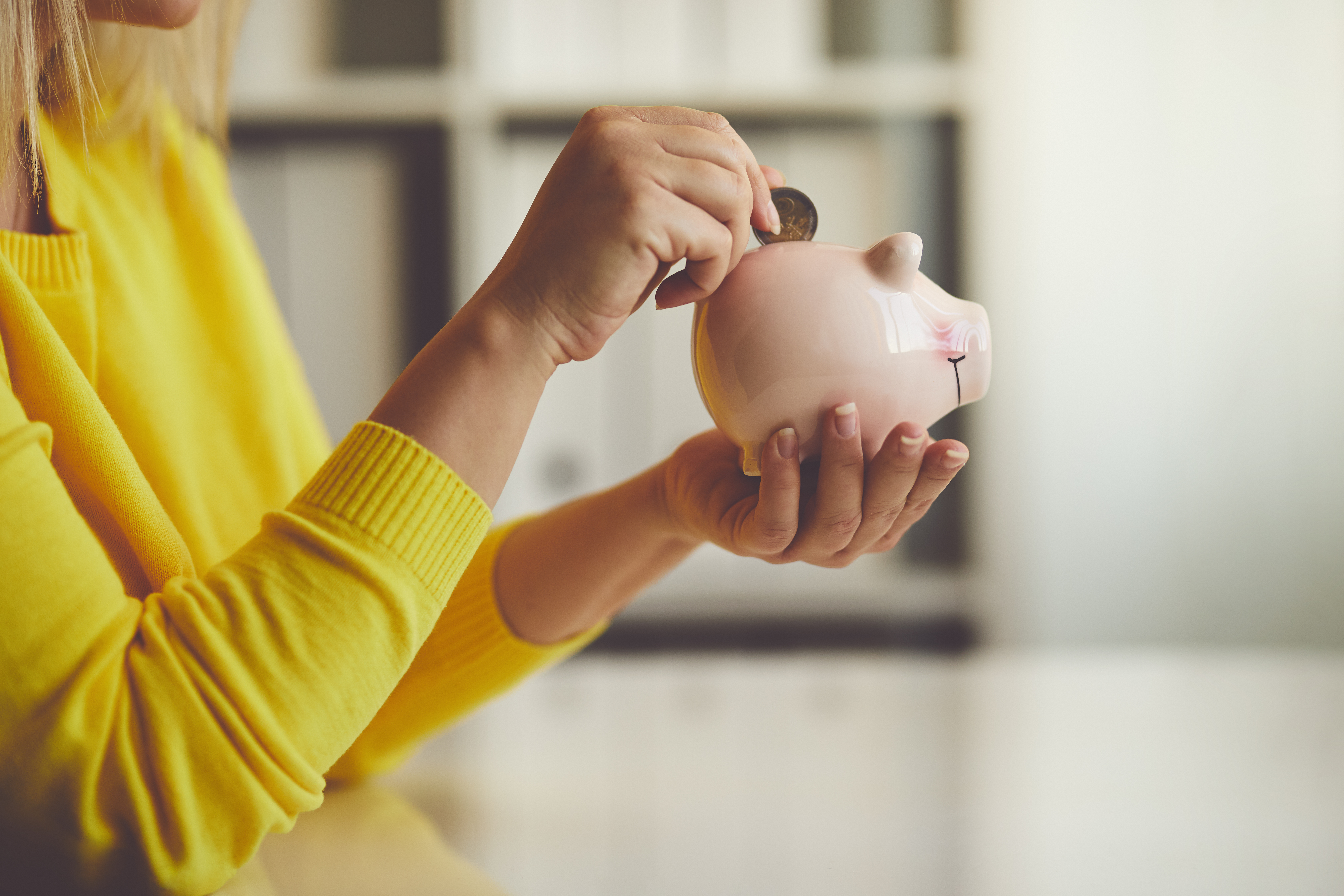 Woman inserts a coin into a piggy bank, toned image